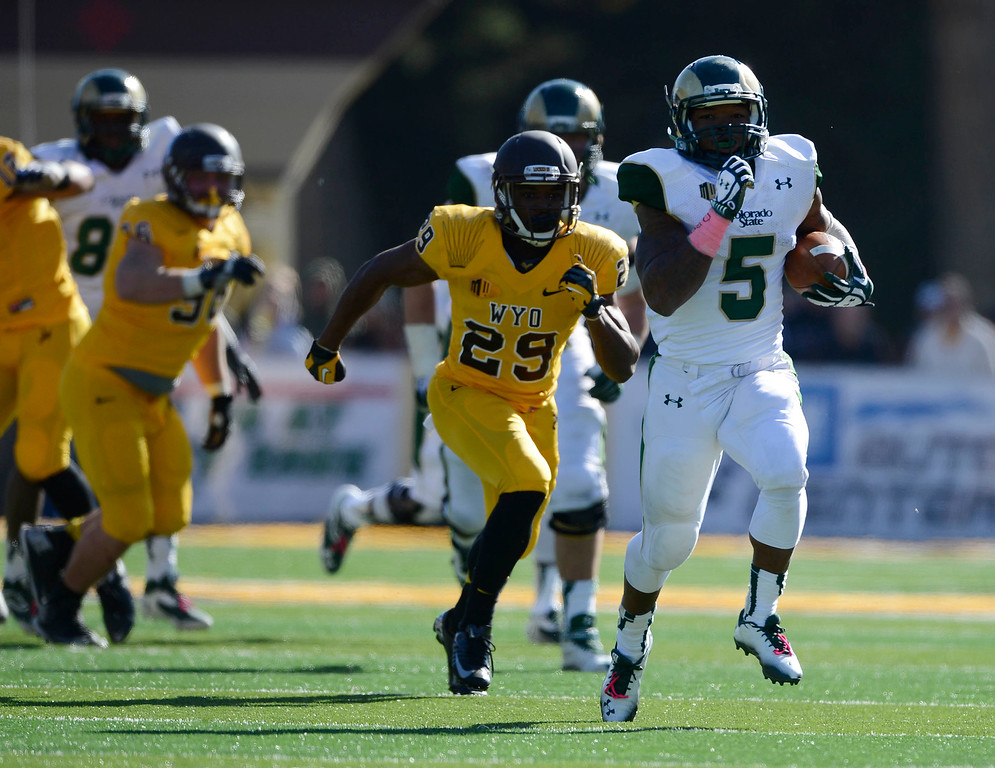 . Colorado State RB, Kapri Bibbs, center, escapes numerous Wyoming defenders including, Tim Haynes, #29, and heads to the endzone for a touchdown in the fourth quarter at Jonah Field at War Memorial Stadium Saturday, October 19, 2013. Rams won 52-22. (Photo By Andy Cross/The Denver Post)
