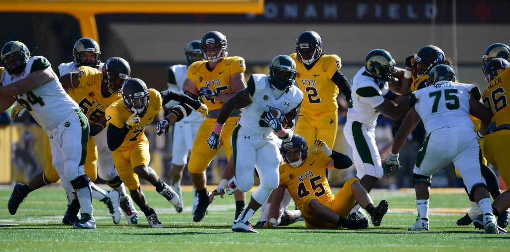 . Colorado State RB, Kapri Bibbs, center, escapes numerous Wyoming defenders and heads to the endzone for a touchdown in the fourth quarter at Jonah Field at War Memorial Stadium Saturday, October 19, 2013. Rams won 52-22.  (Photo By Andy Cross/The Denver Post)