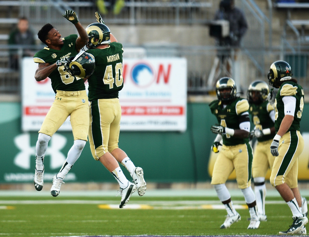 . Rashard Higgins (82) and Max Morgan (4) of Colorado State University celebrate after stopping the 4th down gamble by University of Nevada in the 4th quarter of the game at Hughes Stadium in Fort Collins, Colorado on November 09, 2013. CSU won 38-17. (Photo by Hyoung Chang/The Denver Post)