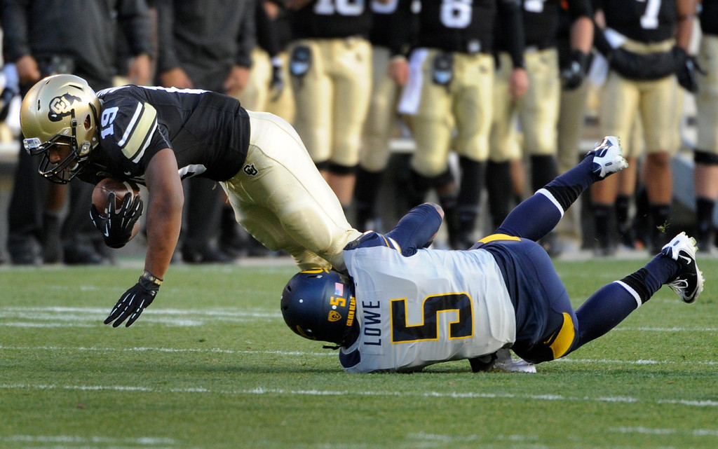 . BOULDER, CO - NOVEMBER 16: Michael Adkins II (19) dives forward for extra yards with Cal\'s Michael Lowe (5) holding on for the tackle. The University of Colorado football team takes on the University of California in the first quarter at Folsom Field in Boulder. (Photo by Kathryn Scott Osler/The Denver Post)