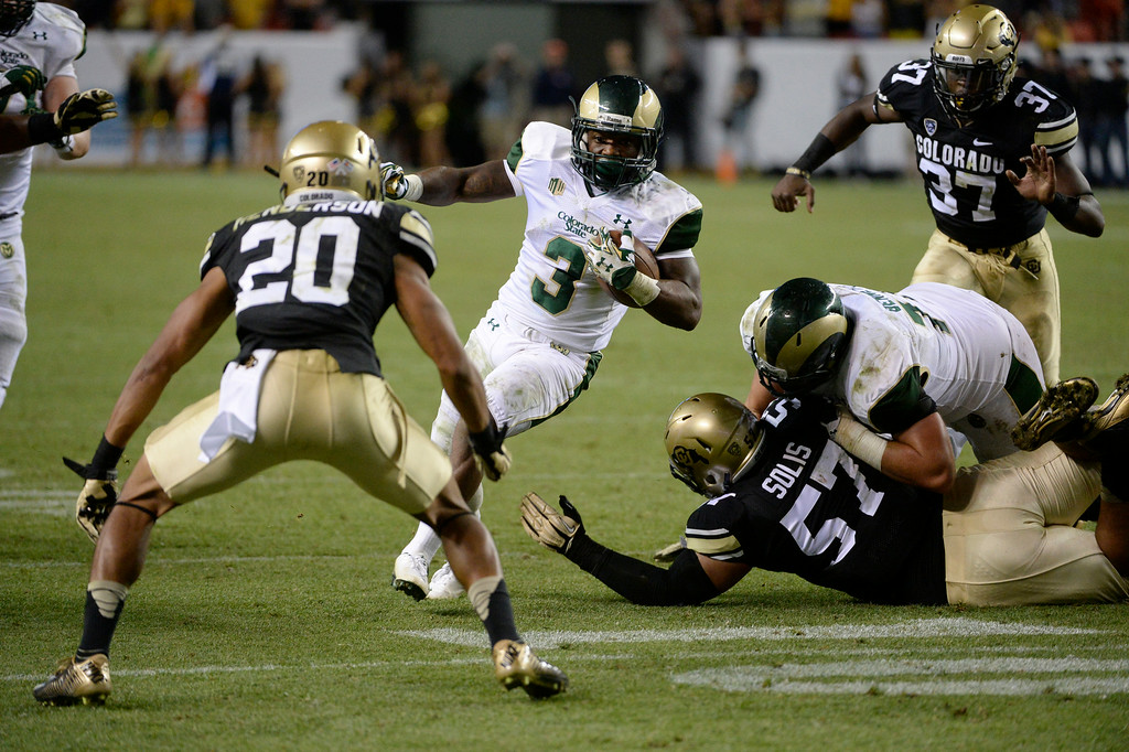 . DENVER, CO. - AUGUST 29: Colorado State RB, Treyous Jarrells, finds a hole to run through against the Colorado University defenders in the third quarter at the Rocky Mountain Showdown at Sports Authority Field at Mile High Friday evening, August 29, 2014. (Photo By Andy Cross / The Denver Post)