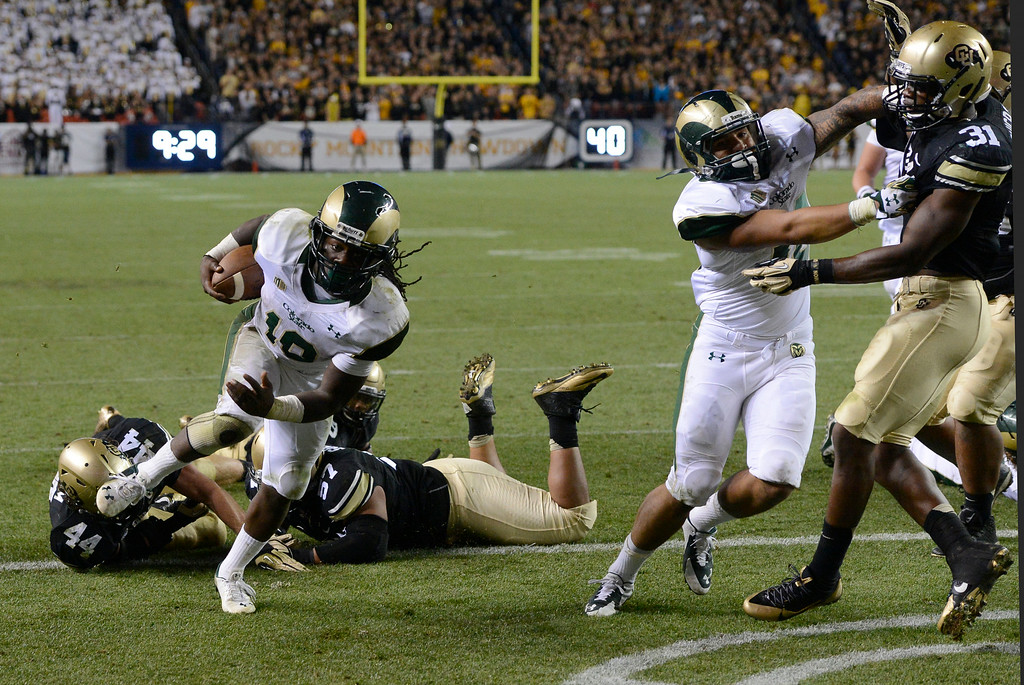 . DENVER, CO. - AUGUST 29:  Colorado State RB, Dee Hart scores a touchdown against CU defenders, Addison Gillam, #44, left, and  and Christian Shaver, $#47, in the fourth quarter at the Rocky Mountain Showdown at Sports Authority Field at Mile High Friday evening, August 29, 2014. The Rams went on to win 31-17. (Photo By Andy Cross / The Denver Post)