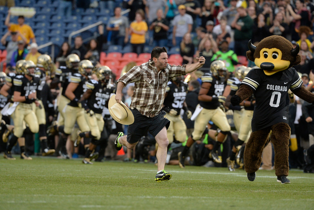 . DENVER, CO. - AUGUST 29: Denver Post sports columnist, Benjamin Hochman, runs out onto the field with the Colorado Buffaloes football team behind Ralphie the Buffalo during pre-game before CU played CSU the Rocky Mountain Showdown at Sports Authority Field at Mile High Friday evening, August 29, 2014. Phillip Lindsay, gets in on the play. (Photo By Andy Cross / The Denver Post)