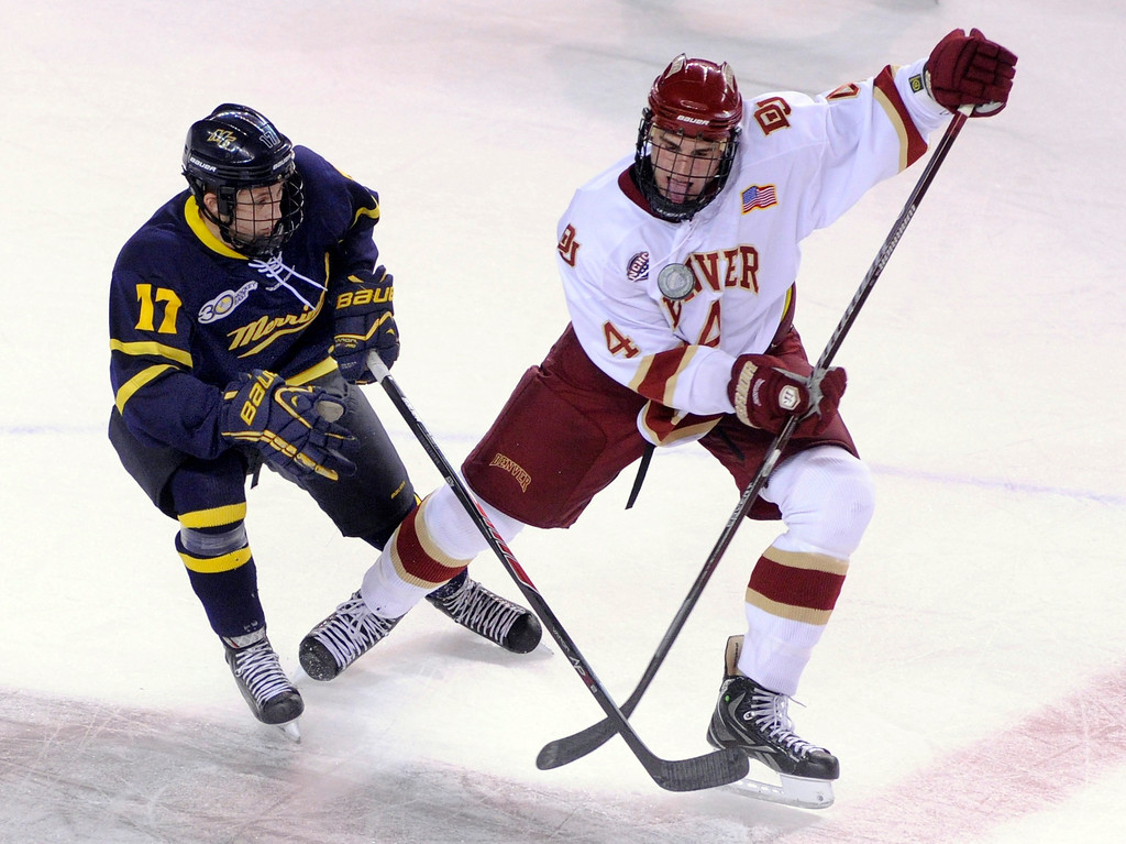 . DENVER, CO. - OCTOBER 11: Denver defenseman Josiah Didier (4)  Merrimack wing Ben Bahe (17) fought for the puck in the first period. The University of Denver men\'s hockey team hosted Merrimack at Magness Arena Friday night, October 11, 2013. Photo By Karl Gehring/The Denver Post