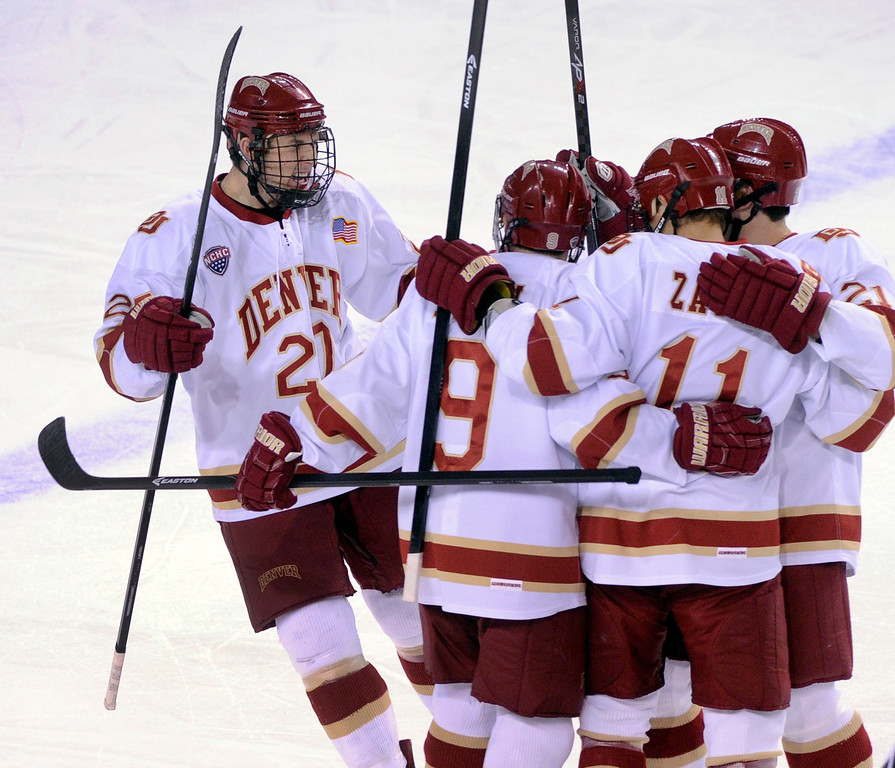 . DENVER, CO. - OCTOBER 11: The Pioneers celebrated after center Daniel Doremus (19) deflected a shot past Merrimack goaltender Sam Marotta in the first period. The University of Denver men\'s hockey team hosted Merrimack at Magness Arena Friday night, October 11, 2013. Photo By Karl Gehring/The Denver Post