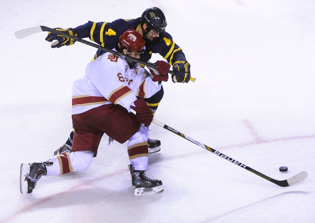 . DENVER, CO. - OCTOBER 11: Denver left wing Trevor Moore (8) tried to get around Merrimack defenseman Jordan Heywood (4) in the second period. The University of Denver men\'s hockey team hosted Merrimack at Magness Arena Friday night, October 11, 2013. Photo By Karl Gehring/The Denver Post
