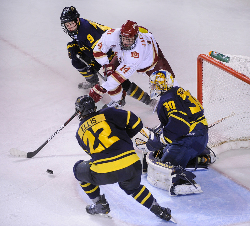 . DENVER, CO. - OCTOBER 11: Denver left wing Larkin Jacobson (14) slapped at the puck in front of Merrimack goaltender Sam Marotta (30) in the second period. The University of Denver men\'s hockey team hosted Merrimack at Magness Arena Friday night, October 11, 2013. Photo By Karl Gehring/The Denver Post