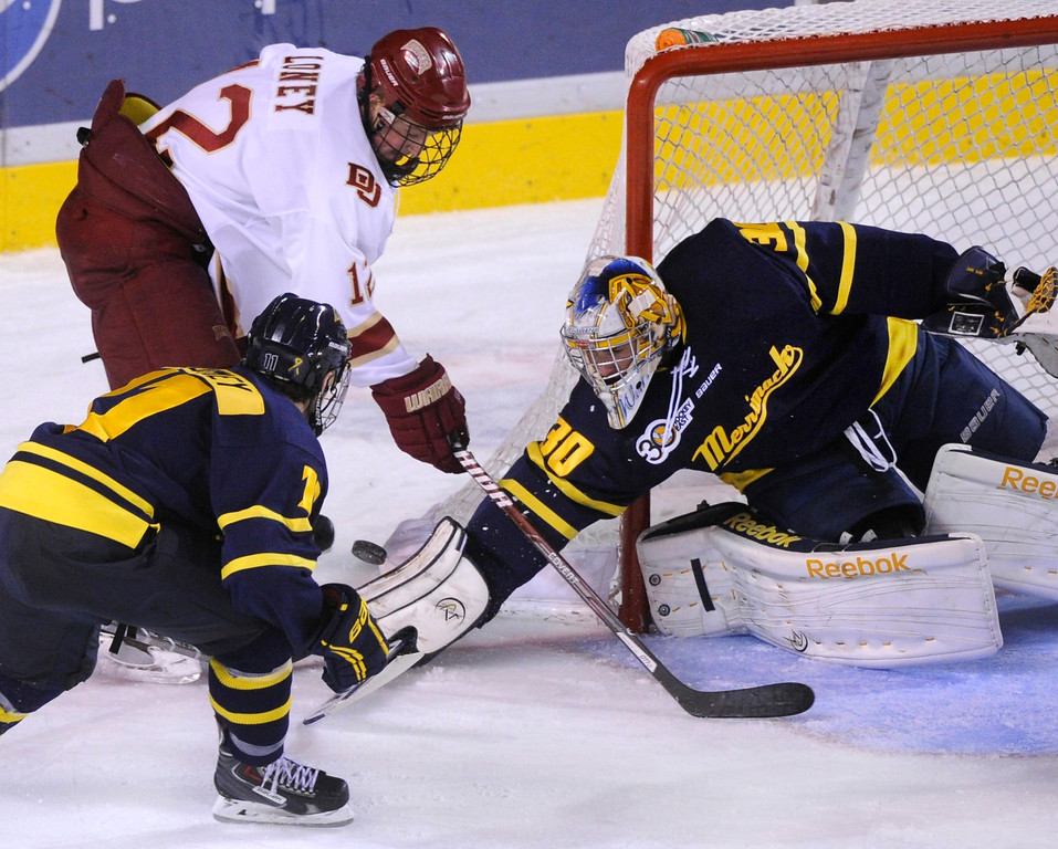 . DENVER, CO. - OCTOBER 11: Denver right wing Ty Loney (12) put some pressure on Merrimack goaltender Sam Marotta (3) late in the third period. The University of Denver men\'s hockey team defeated Merrimack 1-0 at Magness Arena Friday night, October 11, 2013. Photo By Karl Gehring/The Denver Post