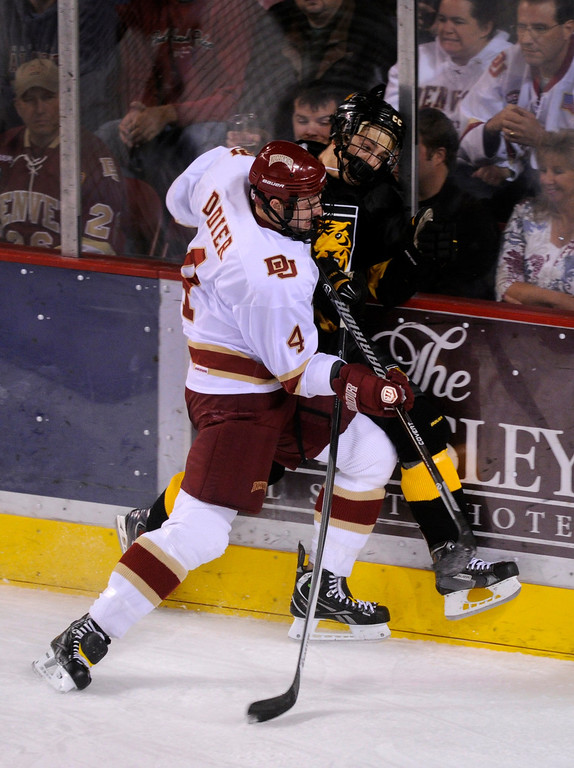 . Denver defenseman Josiah Didier (4) pushed CC wing Hunter Fejes (11) into the glass behind the Pioneer\'s net in the first period. The University of Denver hockey team hosted Colorado College at Magness Arena Saturday night, November 9, 2013. Photo By Karl Gehring/The Denver Post