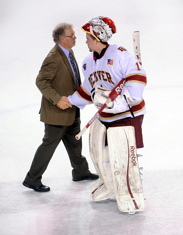 . Colorado College coach Scott Owens congratulated Denver goaltender Sam Brittain following the Pioneers win. The University of Denver hockey team defeated Colorado College 2-1 at Magness Arena Saturday night, November 9, 2013. Photo By Karl Gehring/The Denver Post