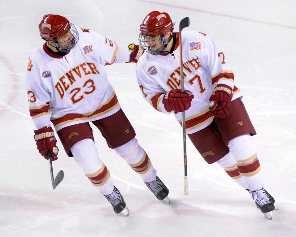 . Denver enter Matt Marcinew (23) congratulated defenseman Will Butcher (7) following his goal in the third period. The University of Denver hockey team defeated Colorado College 2-1 at Magness Arena Saturday night, November 9, 2013. Photo By Karl Gehring/The Denver Post