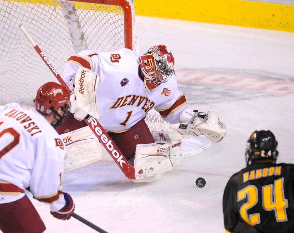 . Denver goaltender Sam Brittain pounced on a loose puck in the third period. The University of Denver hockey team defeated Colorado College 2-1 at Magness Arena Saturday night, November 9, 2013. Photo By Karl Gehring/The Denver Post