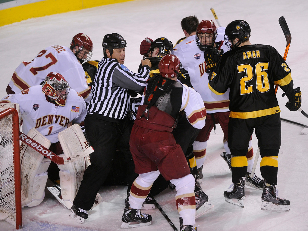 . An official tried to control a skirmish that broke out in front of Denver goaltender Sam Brittain in the second period. The University of Denver hockey team hosted Colorado College at Magness Arena Saturday night, November 9, 2013. Photo By Karl Gehring/The Denver Post