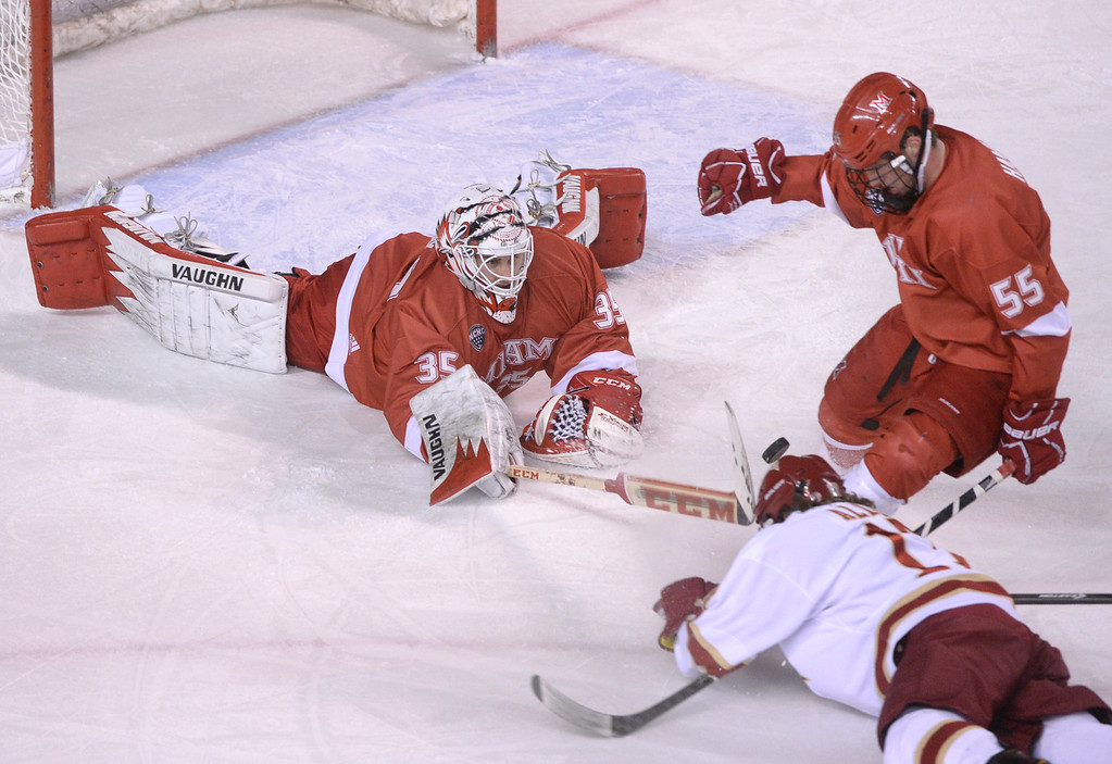 . DENVER, CO - MARCH 7: Miami of Ohio goaltender Ryan McKay (35) pushed the puck away from a rushing Denver wing Garrett Allen (17) in the first period. The University of Denver hockey team hosted Miami of Ohio at Magness Arena Saturday night, March 8, 2014 in Denver, Colorado. (Photo by Karl Gehring/The Denver Post)