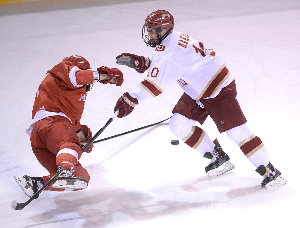 . DENVER, CO - MARCH 7: Denver defenseman David Makowski (10) stopped Miami of Ohio wing Riley Barber (11) in the first period. The University of Denver hockey team hosted Miami of Ohio at Magness Arena Saturday night, March 8, 2014 in Denver, Colorado. (Photo by Karl Gehring/The Denver Post)
