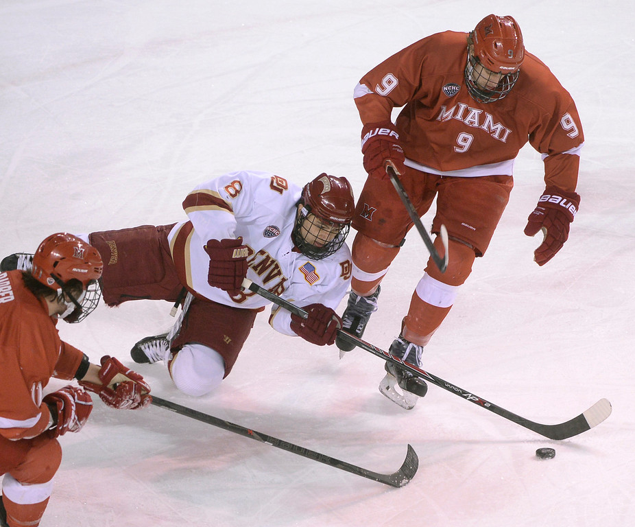. DENVER, CO - MARCH 7: Denver left wing Trevor Moore (8) reached for the puck between Redhawks\' swing Riley Barber (11) and center Sean Kuraly (9) in the first period. The University of Denver hockey team hosted Miami of Ohio at Magness Arena Saturday night, March 8, 2014 in Denver, Colorado. (Photo by Karl Gehring/The Denver Post)