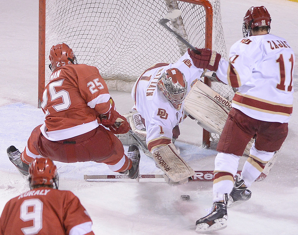 . DENVER, CO - MARCH 7: Sam Brittain made a save on a shot from Miami of Ohio wing Blake Coleman in the third period. The University of Denver hockey team lost to Miami of Ohio 2-1 at Magness Arena Saturday night, March 8, 2014 in Denver, Colorado. It was the last home game of the regular season. (Photo by Karl Gehring/The Denver Post)