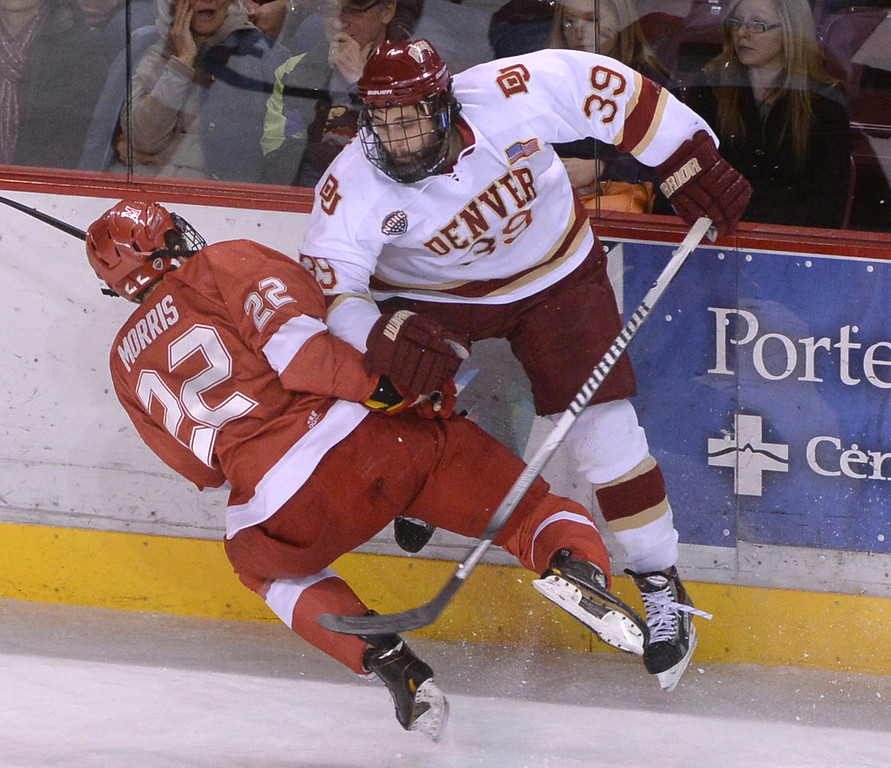 . DENVER, CO - MARCH 7: Redhawks center Kevin Morris (22) checked Denver win Grant Arnold (39) into the boards in the first period. The University of Denver hockey team hosted Miami of Ohio at Magness Arena Saturday night, March 8, 2014 in Denver, Colorado. (Photo by Karl Gehring/The Denver Post)