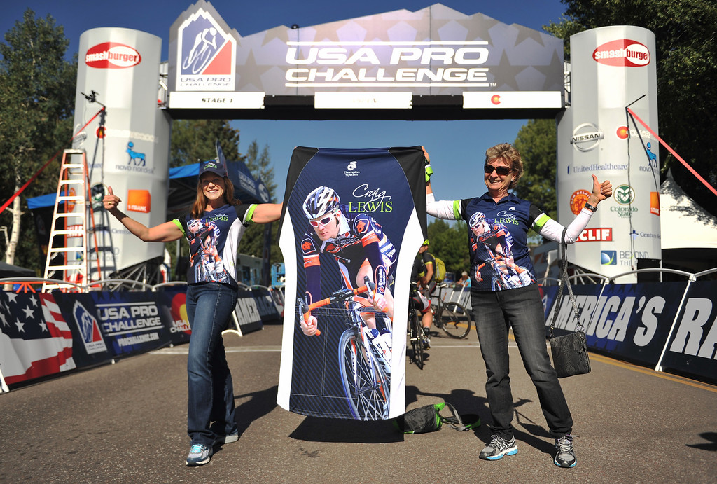 . Bobbie Marshall, aunt of Craig Lewis of Champion System Pro Cycling, left, and her friend Susan Phillips hold a bike jersey to cheer Lewis at the start gate of first stage of the 2013 USA Pro Challenge. (Photo By Hyoung Chang/The Denver Post)