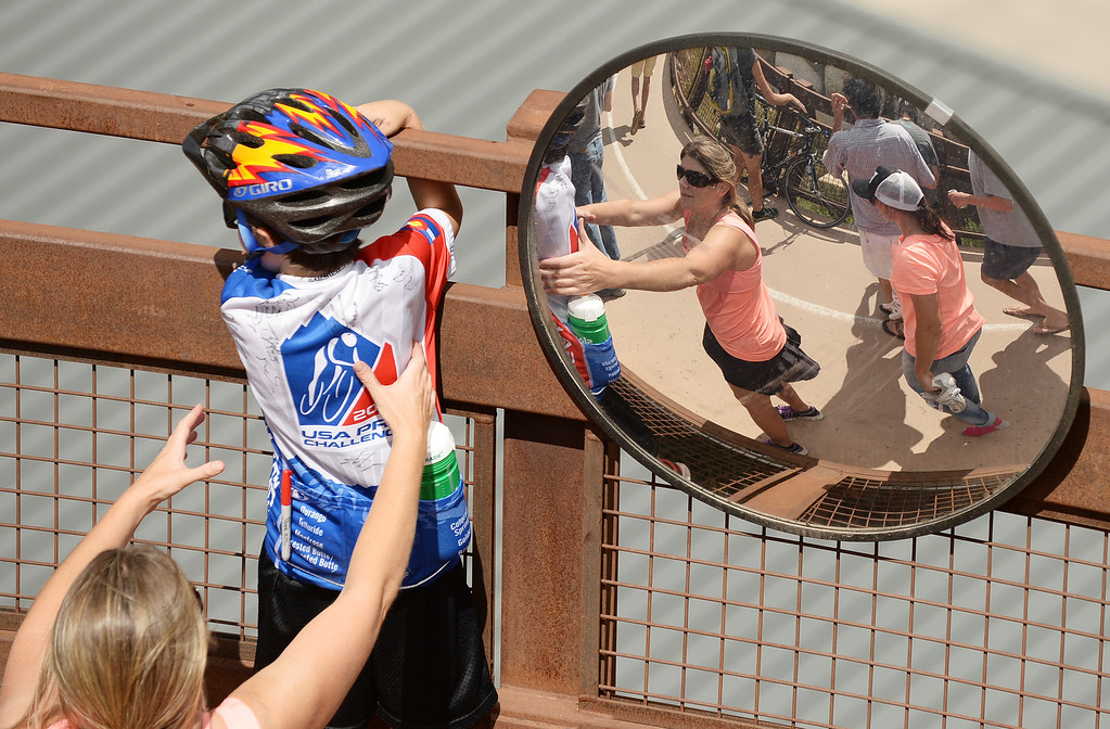 . A young fan watches the pack of cyclists from the bridge during the race. (Photo By Hyoung Chang/The Denver Post)