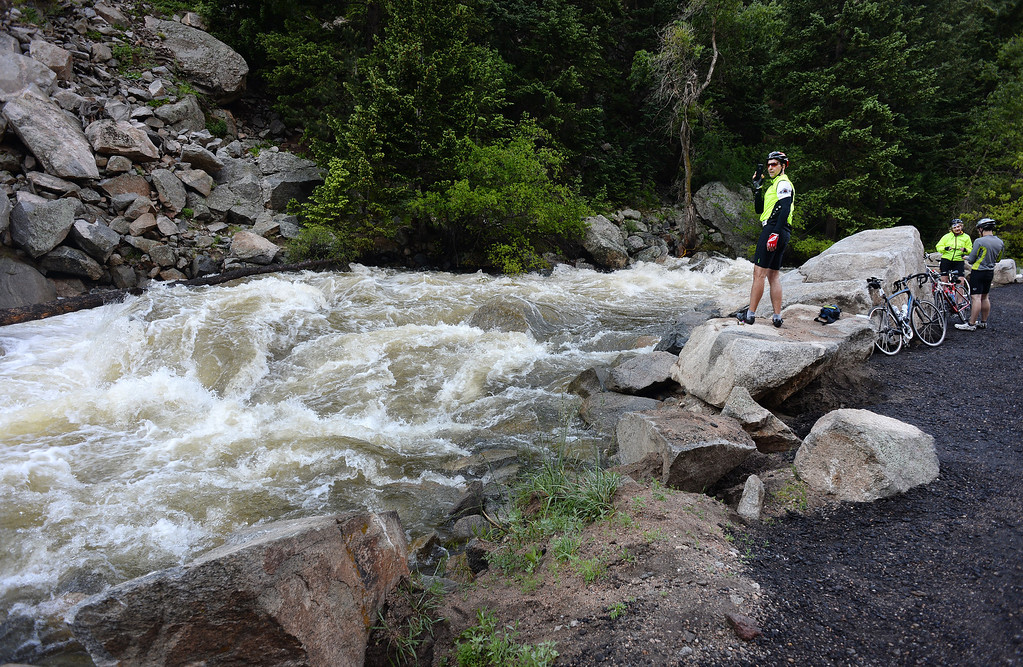 . Cyclists check out the fast moving Boulder Creek as they take a break on their make their way up Boulder Canyon in Boulder (Photo By Helen H. Richardson/ The Denver Post)