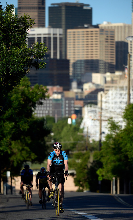 """. DENVER, CO - JUNE 9:  With downtown Denver in the background, instructor Dennis Fitzpatrick rides up the hill on  W. 20th Ave. next to Sports Authority Field as he leads the \""""Bicycle Bootcamp\"""" on Monday, June 9, 2014. The  bootcamp readies riders for climbing mountain passes this summer.  (Denver Post Photo by Cyrus McCrimmon)"""