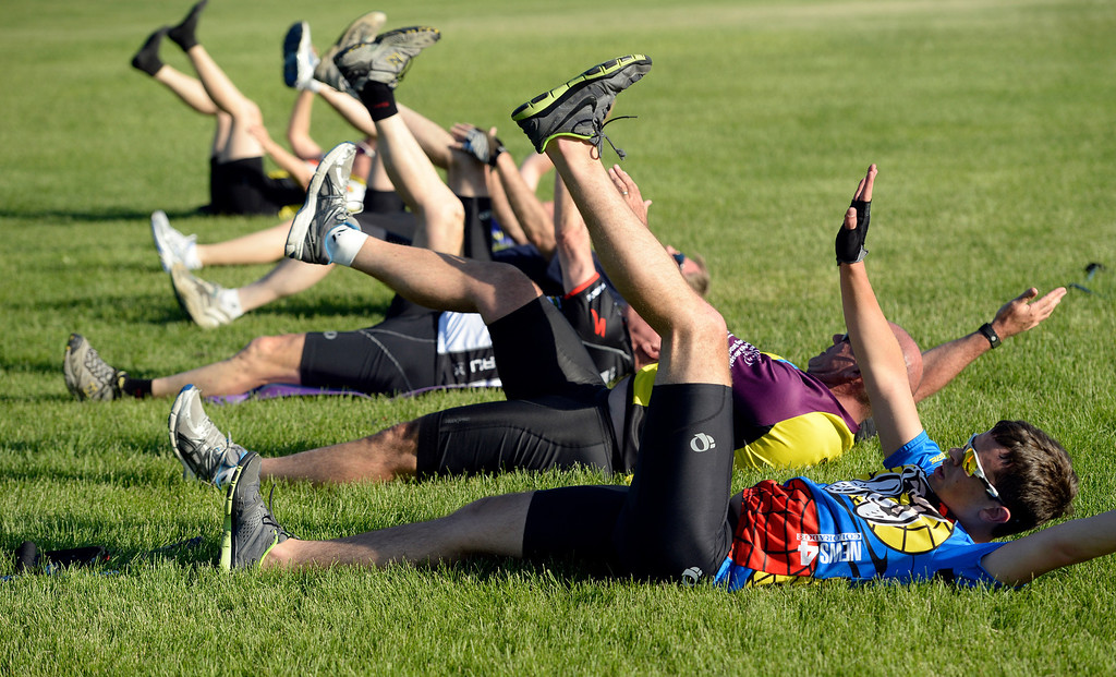 """. DENVER, CO - JUNE 9:  Brody Northcott, right,  and   classmates participate in the \""""Bicycle Bootcamp\"""" at Crescent Park in Denver in the shadow of Sports Authority Field at Mile High on Monday, June 9, 2014. The  bootcamp readies riders for climbing mountain passes this summer. Before riding, they do some core strengthening exercises in the park. (Denver Post Photo by Cyrus McCrimmon)"""