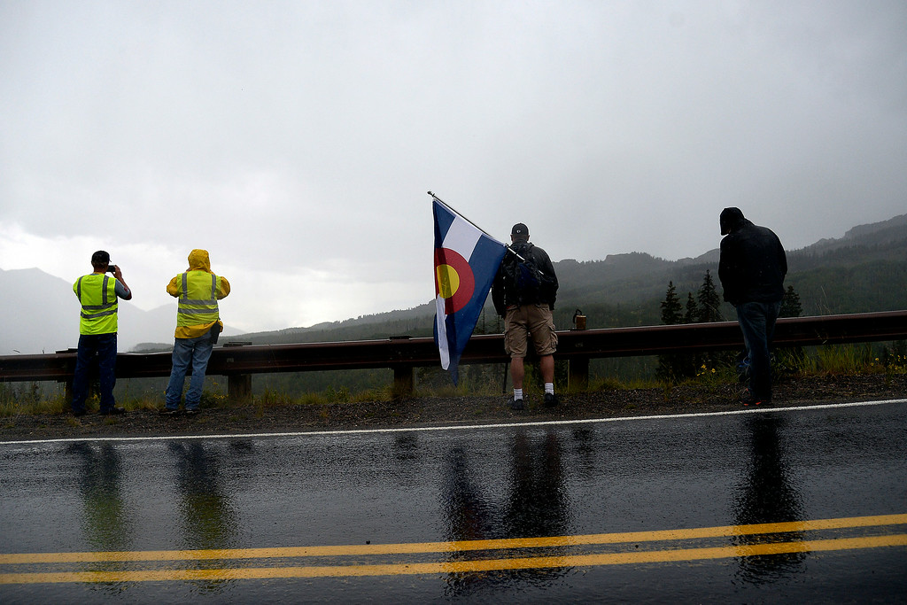 . Keith Byers holds a Colorado state flag as leader Robin Carpenter approaches during stage 2. The USA Pro Challenge stage 2 on Tuesday, August 19, 2014. (Photo by AAron Ontiveroz/The Denver Post)