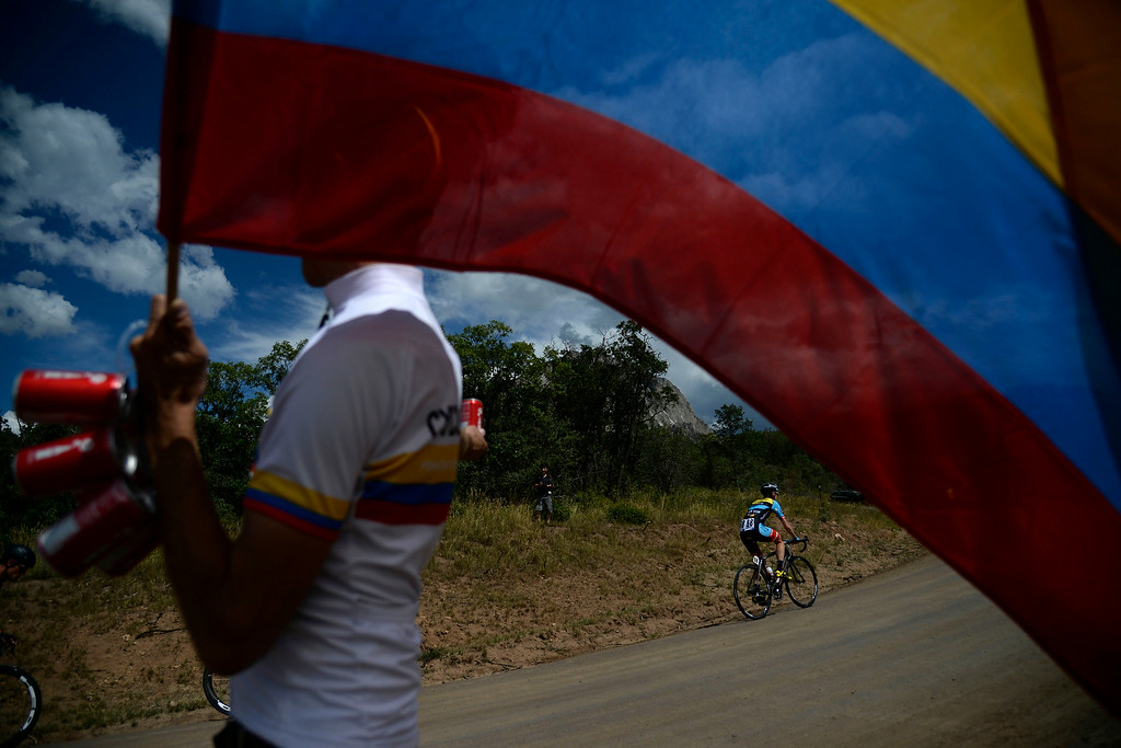 . David Fisher waves a Colombian flag as he cheers on Michael Torckler of Team Smartstop The USA Pro Challenge stage 2 on Tuesday, August 19, 2014. (Photo by AAron Ontiveroz/The Denver Post)