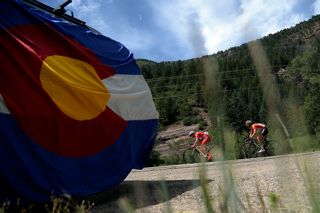 . Riders left to right Jai Crawford of Drapac Pro Cycling and Ben Jacques-Maynes of Jamis-Hagens Berman ride near a large Colorado state flag. The USA Pro Challenge stage 2 on Tuesday, August 19, 2014. (Photo by AAron Ontiveroz/The Denver Post)