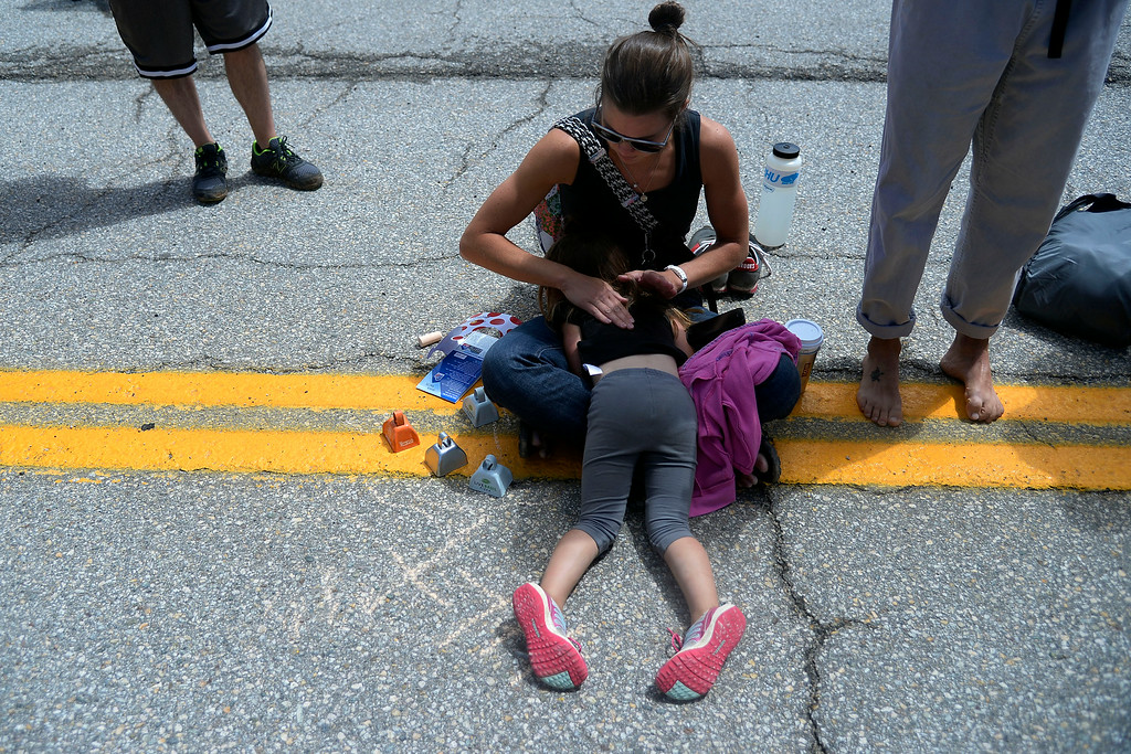 . Anna Thompson plays a beat on her daughter Halsey\'s back as they wait for cyclists to pass during stage 3. The USA Pro Challenge stage 3 on Wednesday, August 20, 2014. (Photo by AAron Ontiveroz/The Denver Post)