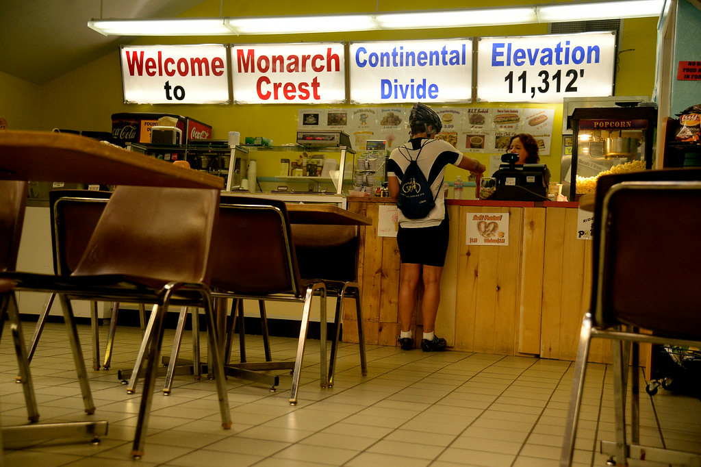 . Laurence Kohler pays Jeanne Pugh at the Mountain Crest cafeteria on Monarch Pass. Hundreds of cyclists filled the highway over Monarch Pass in support of the athletes passing through later in the day. The USA Pro Challenge stage 3 on Wednesday, August 20, 2014. (Photo by AAron Ontiveroz/The Denver Post)