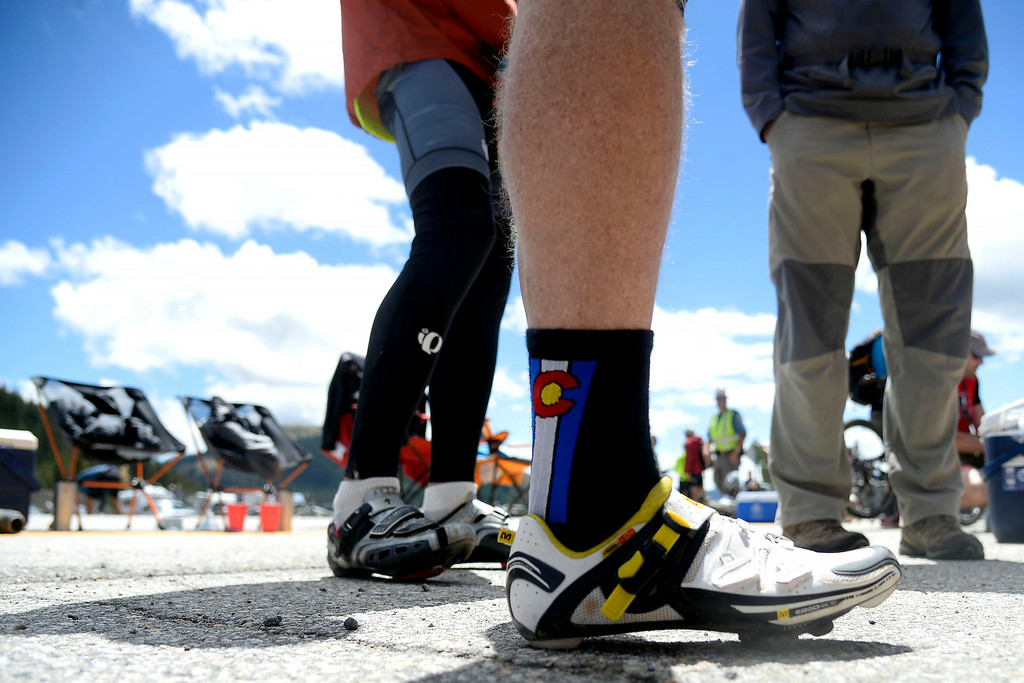 . Michael Haynes wears festive Colorado socks with his cycling shoes as he waits for the riders during stage 3. The USA Pro Challenge stage 3 on Wednesday, August 20, 2014. (Photo by AAron Ontiveroz/The Denver Post)