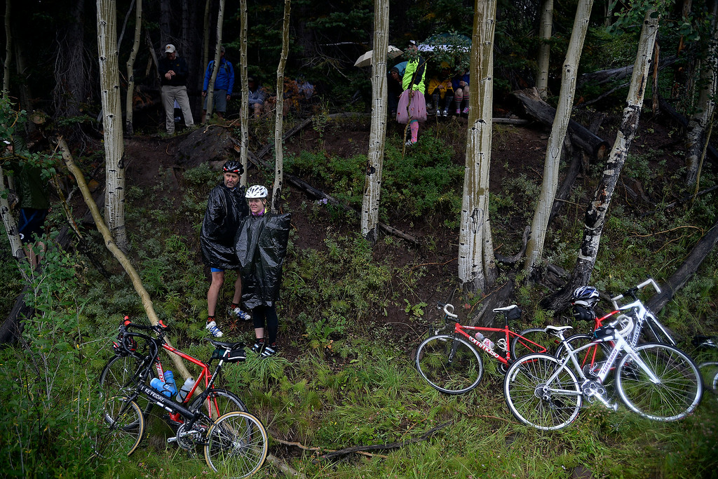 . VAIL, CO - AUGUST 23: Fans take refuge under trees as rain falls at the stage 6 finish line. The USA Pro Challenge stage 6 time trial on Saturday, August 23, 2014. (Photo by AAron Ontiveroz/The Denver Post)