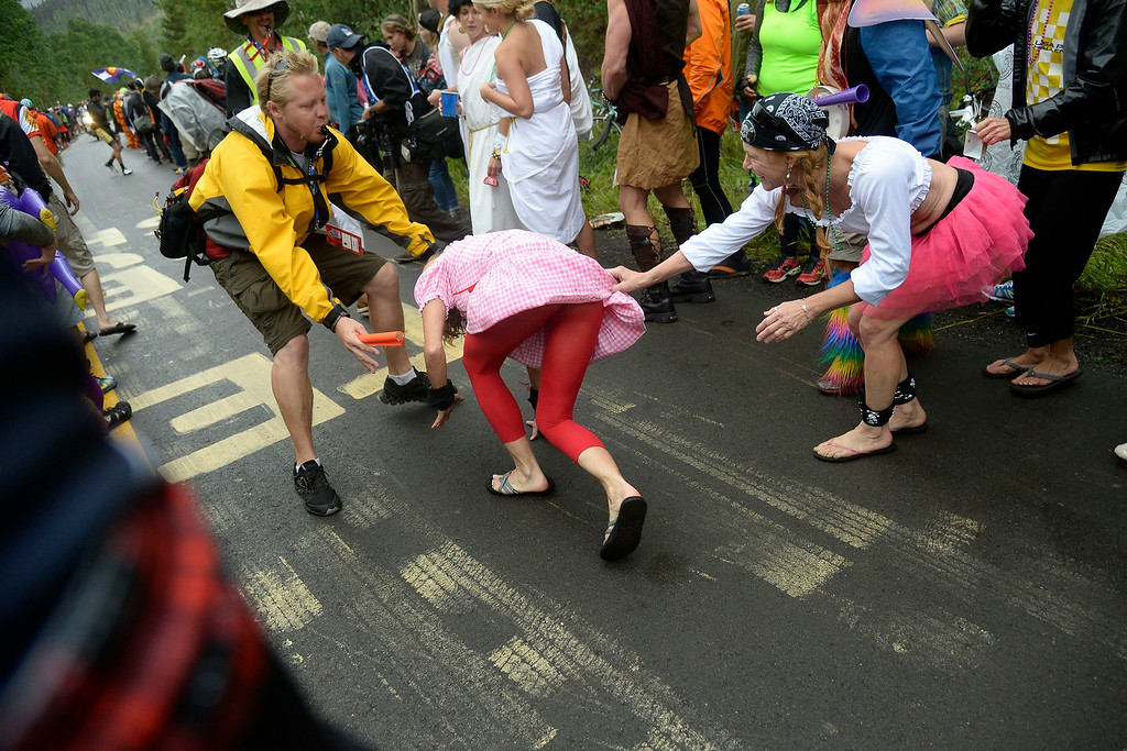 . VAIL, CO - AUGUST 23: A race official helps clear a woman from the track as a racer approaches during stage 6. The USA Pro Challenge stage 6 time trial on Saturday, August 23, 2014. (Photo by AAron Ontiveroz/The Denver Post)
