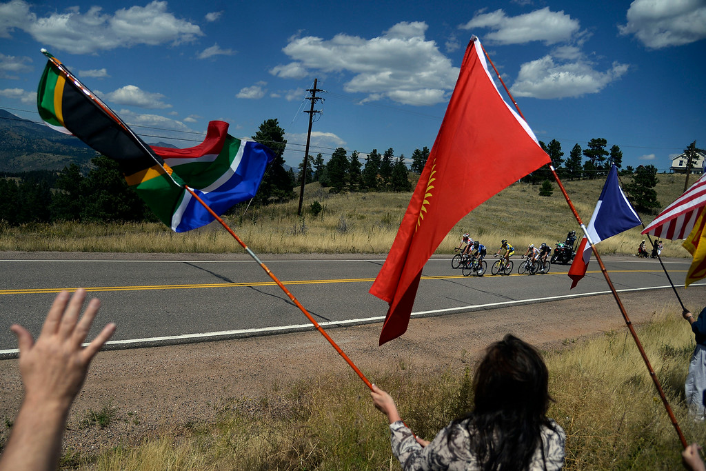 . Fans wave flags for riders as they make a descent down Lookout Mountain. The USA Pro Challenge stage 7 on Sunday, August 24, 2014. (Photo by AAron Ontiveroz/The Denver Post)