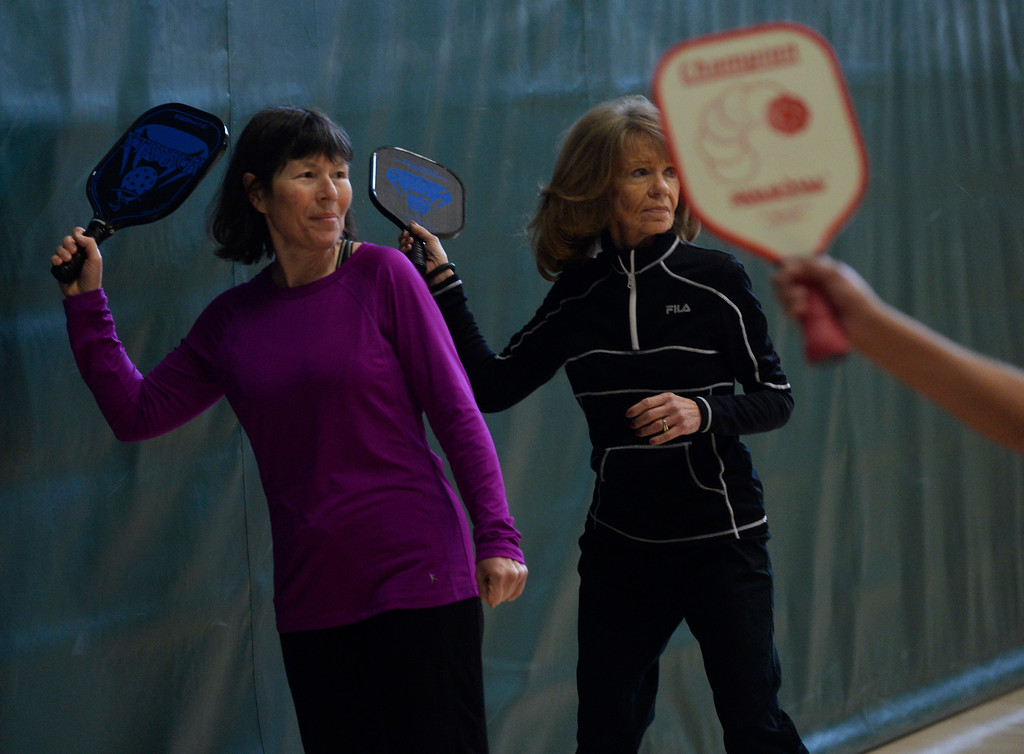 . Pickleball players, Kris Fletcher, left, and Cheryl Mee,  practice the basics during a Pickleball skills and drills session at the Apex Center Tuesday morning, February 11, 2014. Pickleball combines elements of tennis, ping-pong and badminton that is played on a court, half the size of a tennis court. (Photo By Andy Cross / The Denver Post)