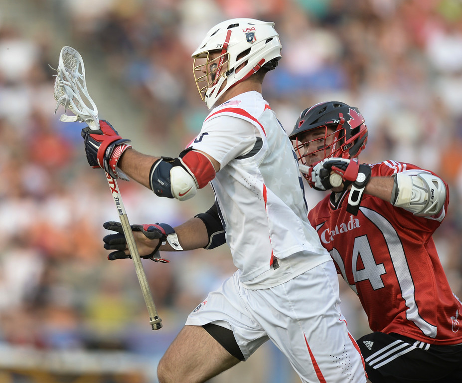 . U.S. attack Garrett Thul, front, carries the ball past Canada midfielder Jordan MacIntosh during the first half of an FIL World Lacrosse Championship game Saturday, July 19, 2014, in Commerce City, Colo. (AP Photo/The Denver Post, Karl Gehring)