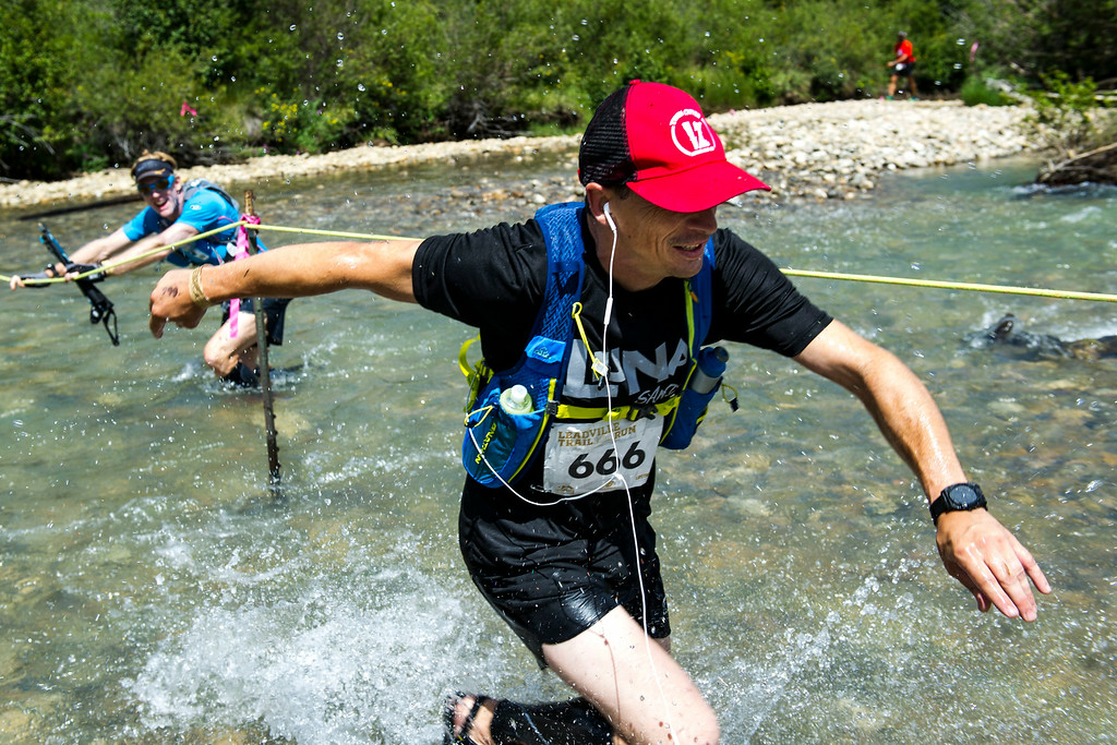 . Cole Chlouber #666 runs past another runner as they make their way across Lake Creek during the 2014 Leadville Trail 100 ultramarathon on Saturday, August 16, 2014 in Twin Lakes, Colorado.  (Photo by Kent Nishimura/The Denver Post)