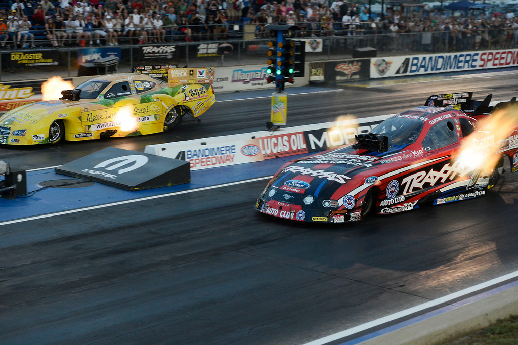 . MORRISON, CO - JULY 19:  NHRA Funny Car drag racers, Courtney Force, bottom, and Johnny Gray, top, race each other during qualifying at the Mopar Mile-High Nationals Friday evening at Bandimere Speedway, July 19, 2013.  (Photo By Andy Cross/The Denver Post)