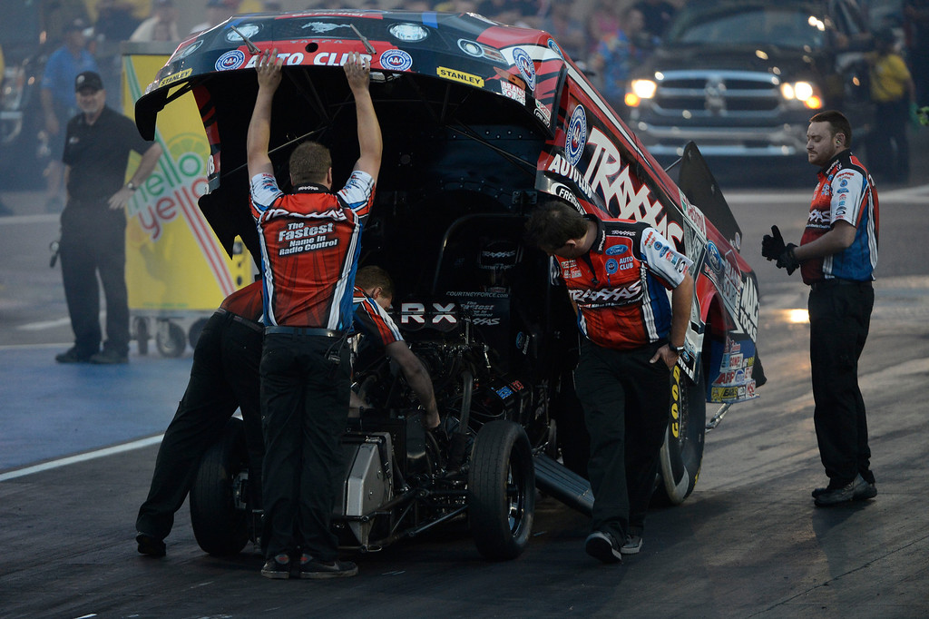 . MORRISON, CO - JULY 19:  Crews for NHRA Funny Car drag racer, Courtney Force, lift the shell of her dragster to make last minute adjustments before Force raced Johnny Gray during qualifying at the Mopar Mile-High Nationals Friday evening at Bandimere Speedway, July 19, 2013.  (Photo By Andy Cross/The Denver Post)