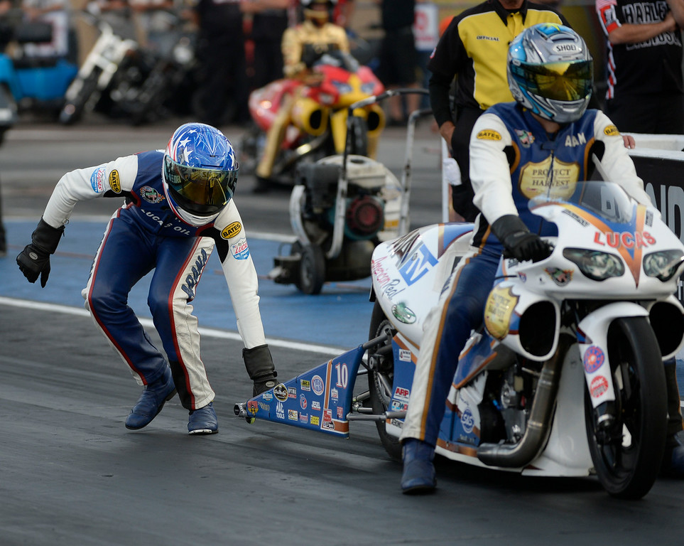 . MORRISON, CO. - JULY 18:  Pro Stock motorcycle rider, Hector Arana Jr. left, tries to realign his brother\'s bike, Adam Arana,  at the start tree Hector Arana, in the staging area Friday evening, July 18, 2014 during the 2014 Mopar Mile High NHRA Nationals at Bandimere Speedway. (Photo By Andy Cross / The Denver Post)