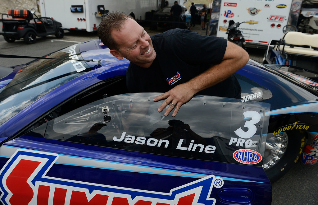 . MORRISON, CO. - JULY 18:  Pro Stock driver, Jason Line has a laugh with a fan as he guides his race car to the scales to be weighed Friday afternoon, July 18, 2014 at the 2014 Mopar Mile High NHRA Nationals at Bandimere Speedway. (Photo By Andy Cross / The Denver Post)