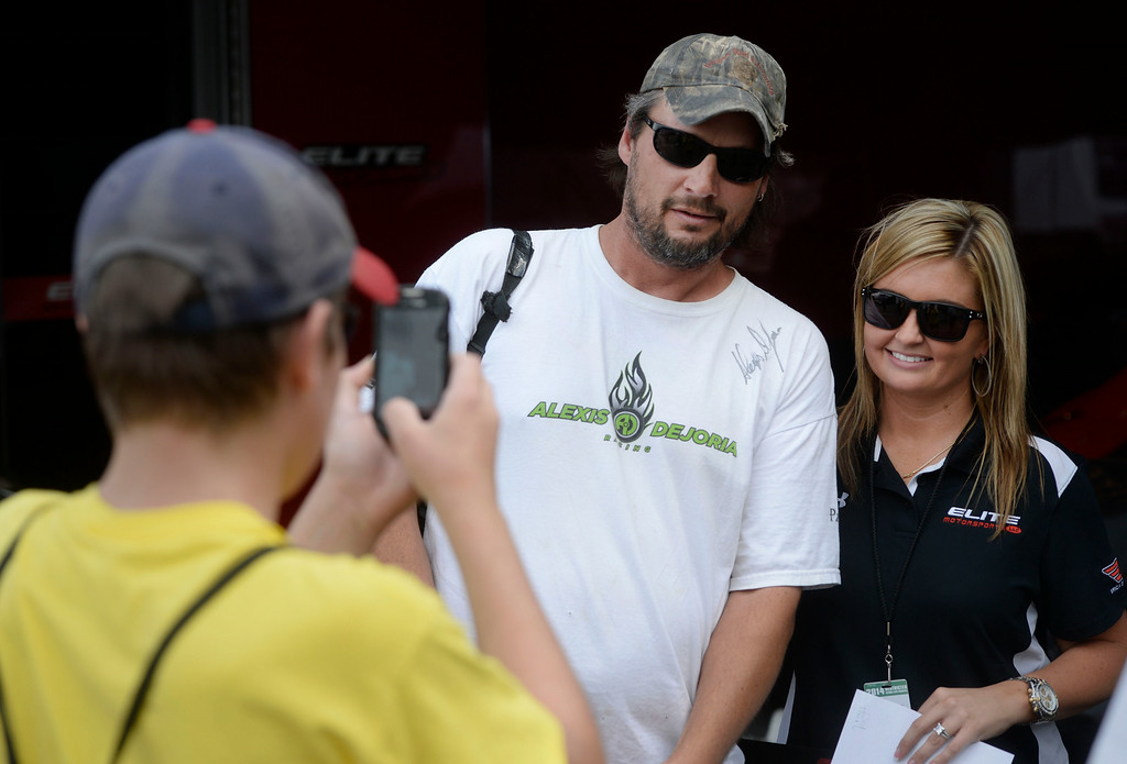 . MORRISON, CO. - JULY 18:  NHRA drag racing fan, Chadd <cq> Beavers, center, has his picture taken with Pro Stock race car driver, Erica Enders-Stevens, right, by his son, Jason, 15,  in the pits Friday afternoon, July 18, 2014 at the 2014 Mopar Mile High NHRA Nationals at Bandimere Speedway. (Photo By Andy Cross / The Denver Post)