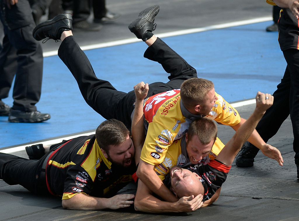 . J.R. Todd\'s crew, Stephen Hashey (L) Dustin Cowen, top, Jesse Snyder (middle) and Adam Shultz bottom celebrate his win over Brittany Force in the Top Fuel competition finals during the MOPAR Mile High Nationals July 20, 2014 at Bandimere Speedway. (Photo by John Leyba/The Denver Post)