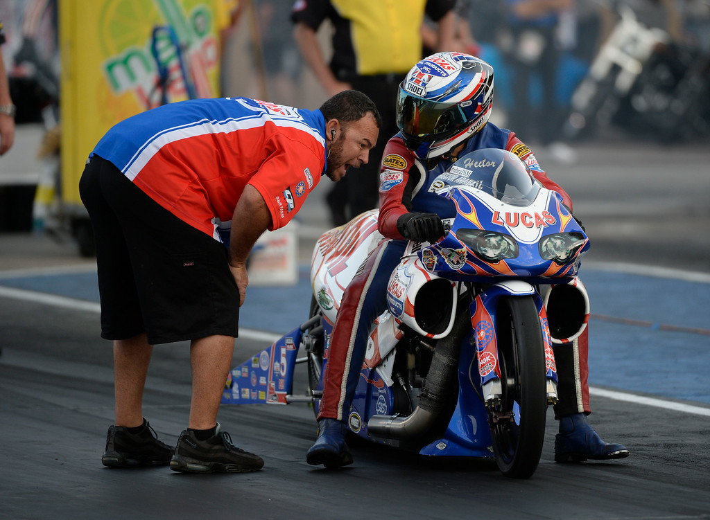 . MORRISON, CO. - JULY 18:  Pro Stock motorcycle rider, Hector Arana, gets last minute advice from a crew member at the start line Friday evening, July 18, 2014 during the 2014 Mopar Mile High NHRA Nationals at Bandimere Speedway. (Photo By Andy Cross / The Denver Post)