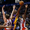 Los Angeles Lakers' Kobe Bryant (C) goes to the basket against Toronto Raptors' Aaron Gray (L) and Ed Davis during the first half of their NBA basketball game in Toronto, January 20, 2013.     REUTERS/Mark Blinch