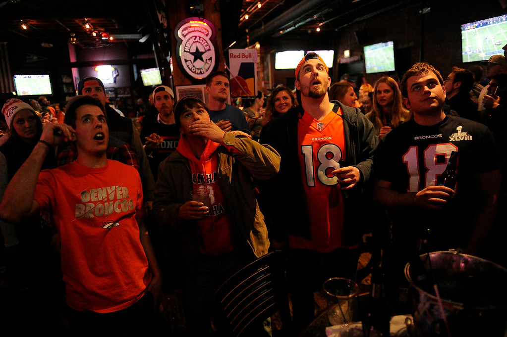 . Tony Grabau, 26, left, Evan Tischhauser, 26, Adam Frieler, 26, and Aaron Tischhauser, 24, cheer on the Broncos in Super Bowl XLVIII at Jackson\'s Bar in Denver, Colorado on February 2, 2014. (Photo by Seth McConnell/The Denver Post)