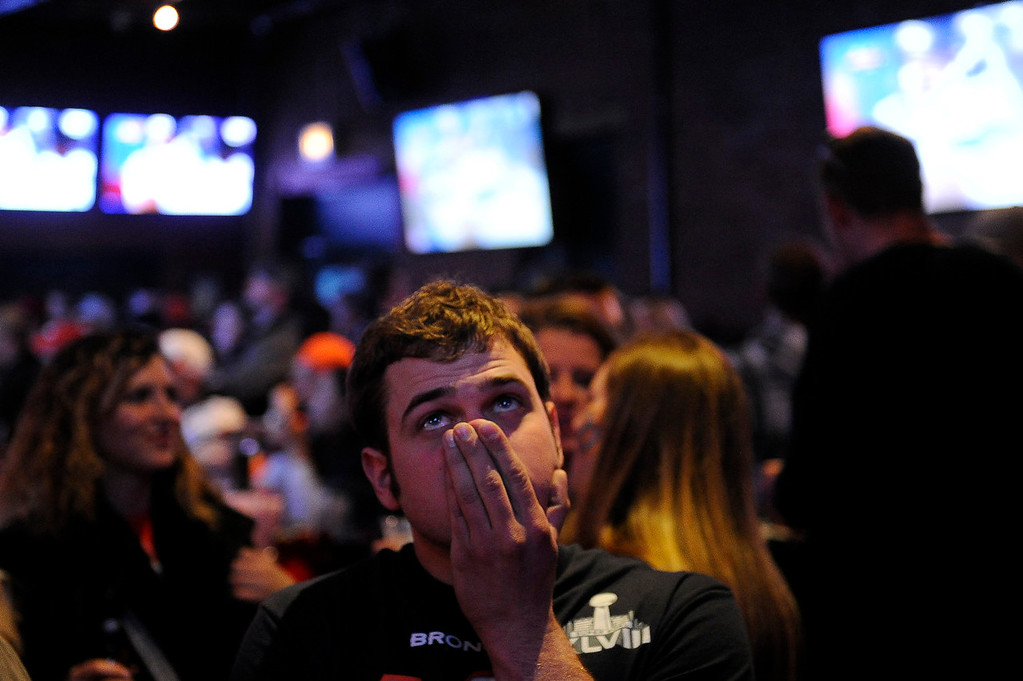 . Aaron Tischhauser, 24, covers his face as he watches the Broncos drive the ball down field in Super Bowl XLVIII at Jackson\'s Bar in Denver, Colorado on February 2, 2014. (Photo by Seth McConnell/The Denver Post)