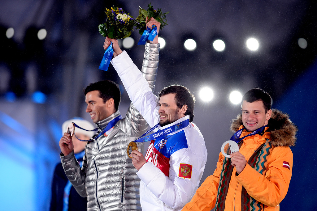 . Gold medalist Alexander Tretiakov (center) of Russia waives his flowers on the stage with silver medalist Martins Dukurs of Latvia (right) and bronze medalist Matthew Antoine of the United States (left) join the celebration during the medals ceremony for the men\'s skeleton. Sochi 2014 Winter Olympics on Sunday, February 16, 2014. (Photo by AAron Ontiveroz/The Denver Post)